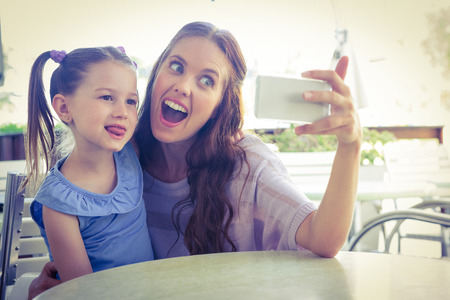 curly hair child: Mother and daughter taking selfie at cafe terrace on a sunny day