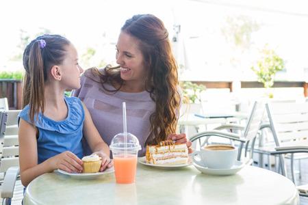 alimentos y bebidas: Madre e hija disfrutando de pasteles en la terraza del café en un día soleado