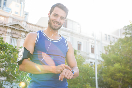 watch city: Portrait of smiling handsome athlete setting heart rate watch in the city