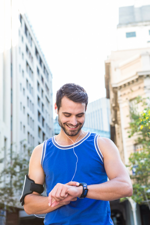 watch city: Smiling handsome athlete setting heart rate watch in the city