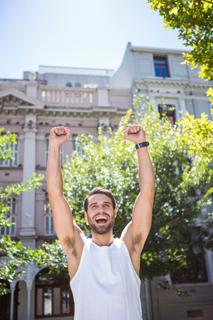 outdoor living: Handsome athlete gesturing victory with arms raised