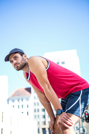 leaning forward: Exhausted athlete leaning forward after an effort on a sunny day