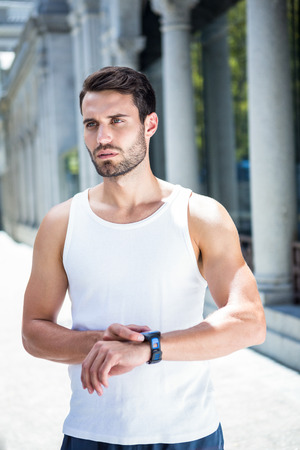 watch city: Concentrated handsome athlete checking heart rate watch in the city