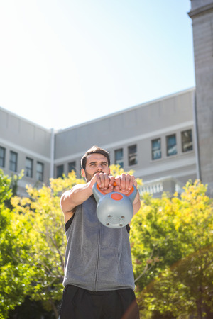 kettle bell: Handsome athlete lifting kettle bell in the city