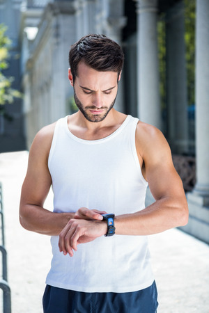 watch city: Concentrated handsome athlete setting heart rate watch in the city