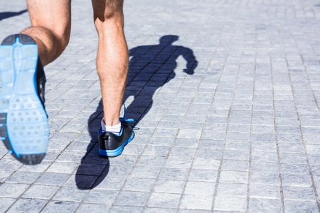 running shoes: Close up view of athletes legs running in the city Stock Photo
