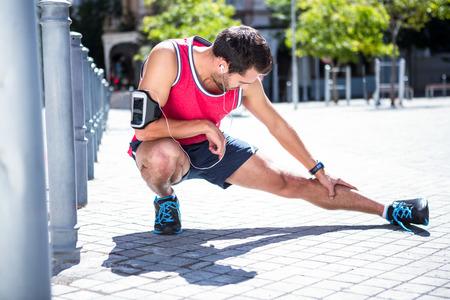 estiramientos: Apuesto atleta de la pierna que se extiende en el suelo en un día soleado