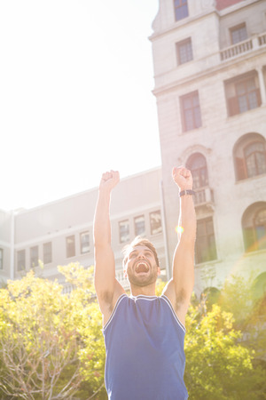 triumphing: Happy handsome athlete triumphing in the city