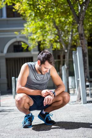 en cuclillas: Eyacular hombre atlético ajustar su cronómetro en un día soleado