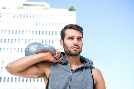 kettle bell: Handsome athlete holding kettle bell in the city