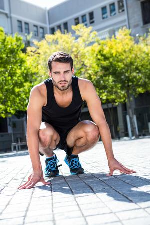 cuclillas: Retrato de un deportista guapo en una posici�n en cuclillas en un d�a soleado Foto de archivo