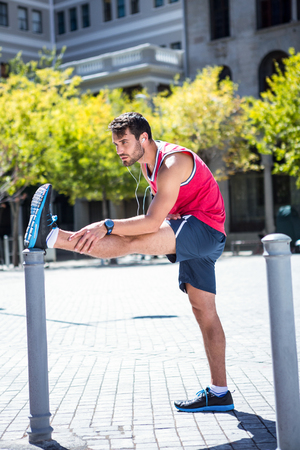 stake: Handsome athlete doing leg stretching on a stake on a sunny day Stock Photo