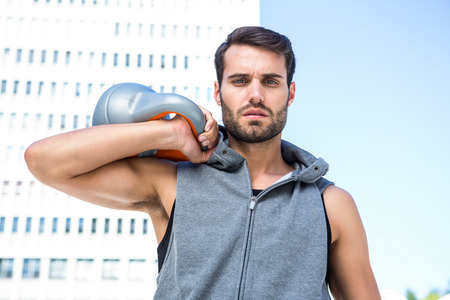 kettle bell: Portrait of handsome athlete holding kettle bell in the city Stock Photo