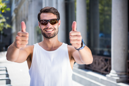 thumbs up: Portrait of smiling handsome athlete doing thumbs up in the city Stock Photo