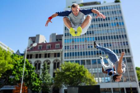 juventud: Amigos felices haciendo parkour en la ciudad en un d�a soleado