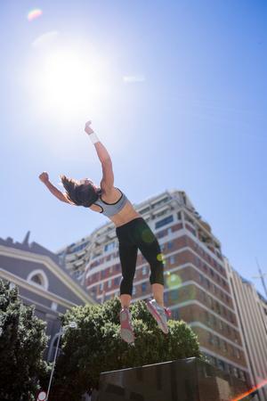 Vrouw doet parkour in de stad op een zonnige dag