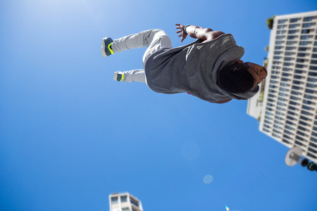 urban culture: Athletic man doing back flip in the city on a sunny day Stock Photo