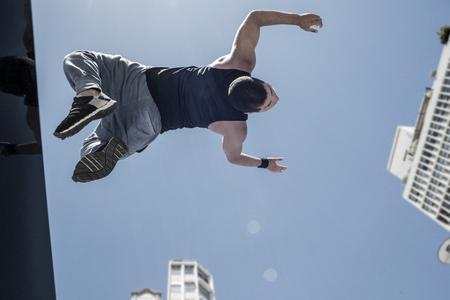 Athletic man doing back flip in the city on a sunny day Reklamní fotografie