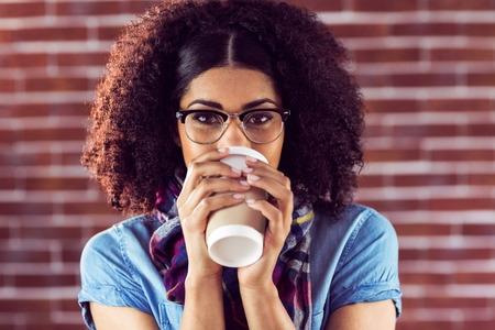 drinking tea: Portrait of attractive hipster drinking out of take-away cup against red brick background