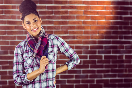 cabello negro: Retrato de una hermosa inconformista sonriente contra una pared de ladrillo rojo