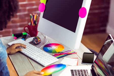 designing: Female graphic designer working at desk against red brick background