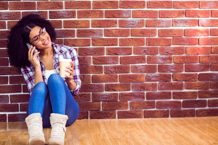 Attractive hipster sitting and phoning with smartphone against red brick background
