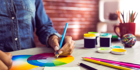 colour chart: Graphic designer drawing on colour chart at workplace Stock Photo