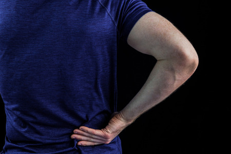 back sprains: Rear view of a man with back pain over over black background