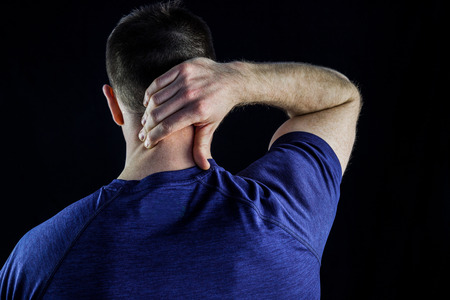 back sprains: Rear view of a man with neck pain over over black background