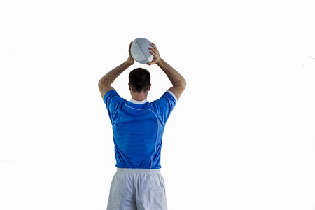 Back view of a rugby player about to throw a rugby ball