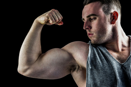 bicep: Handsome bodybuilder flexing his bicep on black background