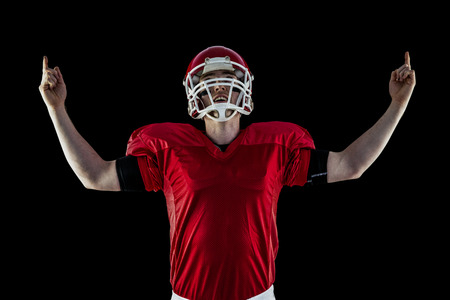 triumphing: American football player triumphing against black background