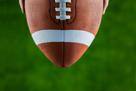 football on the field: Close up view of upheld football on american football field Stock Photo