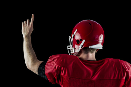 triumphing: Rear view of american football player triumphing against black background