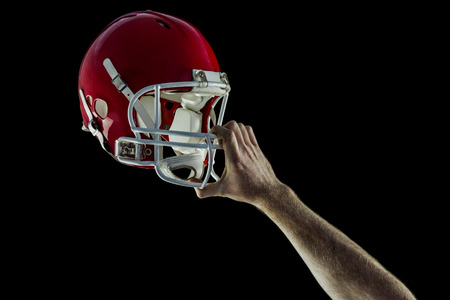 holding up: American football player holding up his helmet against black background