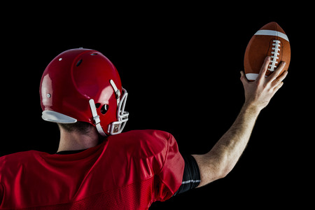 holding up: Rear view of american football player holding up football against black background Stock Photo