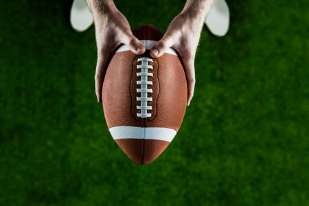 american football ball: American football player holding up football on american football field