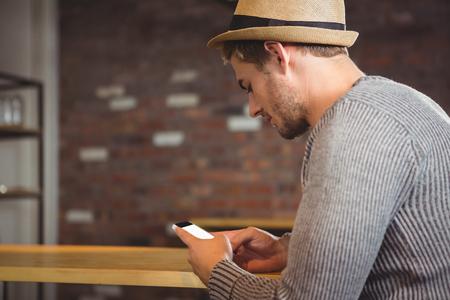 bel homme: Handsome s�ance hipster et les textos au caf� Banque d'images
