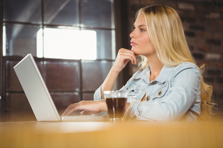 Concentrated blonde having coffee and using laptop at coffee shop