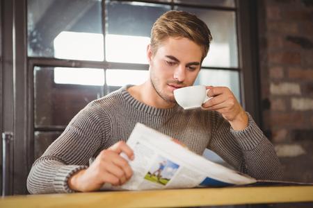 tomando café: Hermoso café hombre bebiendo y leyendo el periódico en la cafetería