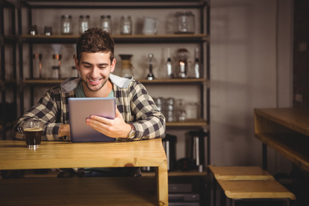 hip: Smiling hipster having coffee and using tablet computer at coffee shop Stock Photo