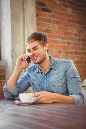 phoning: Handsome man having coffee and phoning at coffee shop