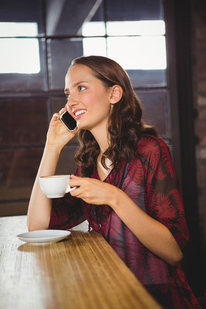 phoning: Smiling brunette drinking coffee and phoning at coffee shop
