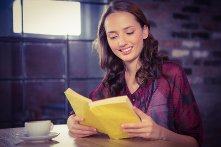 woman reading book: Smiling brunette reading yellow book at coffee shop