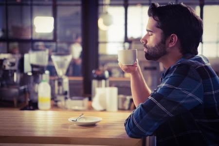 hombre tomando cafe: Hombre preocupante que bebe un café en la cafetería