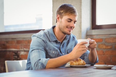 eating pastry: Handsome man enjoying coffee and croissant at coffee shop Stock Photo