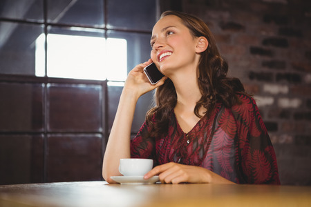 phoning: Smiling brunette having coffee and phoning at coffee shop