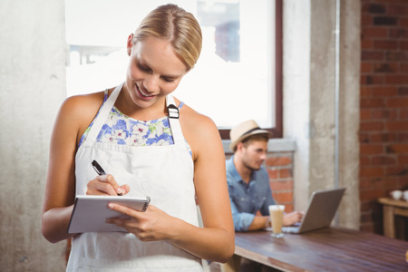 order in: Smiling blonde waitress taking order in front of customer at coffee shop Stock Photo