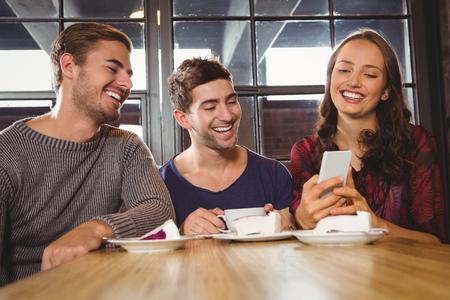 amigos: Amigos de risa que miran smartphone en la cafetería