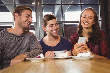 friends: Laughing friends looking at smartphone at coffee shop